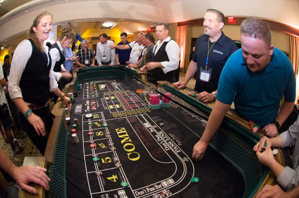 A group of executives are entertained with a game of craps at a casino-themed event.