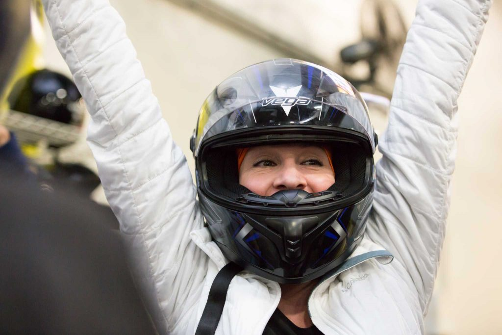 A racer celebrates her win at a go karting outing with her teammates at team building outing.