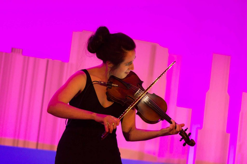 A violinist entertaining a group of executives at a conference with her rendition of a mash up of classic rock songs.